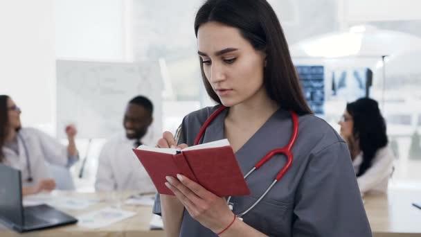 Zaměřil kavkazské lékařka dělat nějakou poznámku v poznámkovém bloku a tým pracovníků mluví na pozadí v nemocnici.
