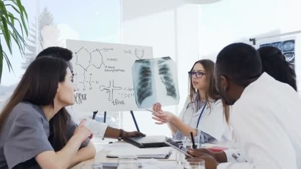 Female doctor holding in hands x-ray film during conference in clinic. Professional doctors of multi ethnic group examine x-ray lungs of patient holding analyze in radiography cabinet