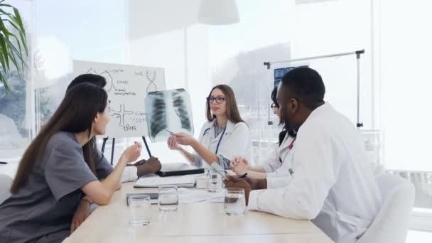 Gruppe qualifizierter Ärzte analysieren Röntgenbilder der Lungen von Patienten. Berufsärzte multiethnischer Gruppen untersuchen Röntgenlungen von Patienten im Röntgenkabinett