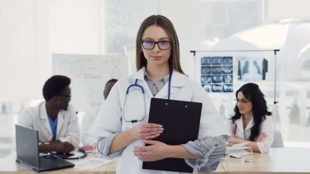 Young female doctor in white coat with stethoscope smiling looking into camera on colleagues background in clinic. Concept of doctors health care, love of medicine