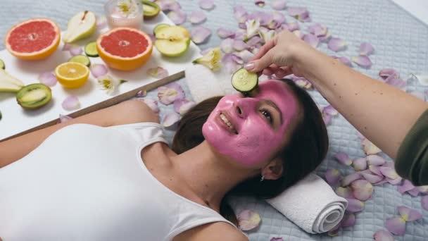 Krásná mladá žena s růžovou maskou uvolňující se v wellness centru, zatímco beautik dával okurku na oči.