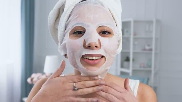 lächelnde Frau repariert verjüngende kosmetische Maske aus weißem Gewebe im Gesicht.