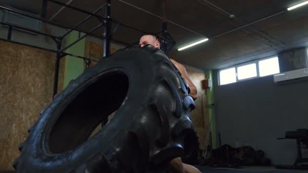 Magabiztos erős ember fricskázó nagy gumiabroncs közben képzés-ban tornaterem.