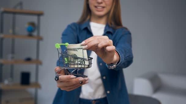 Zavřít ruku mladé ženy držící nákupní vozík s penězi.