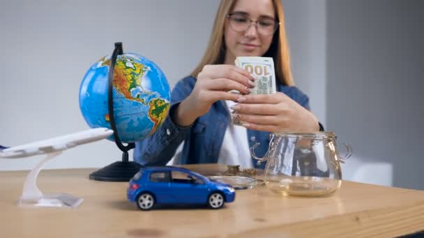 Handsome cute woman taking money from glass jar on the table with globe, toy car and plane.