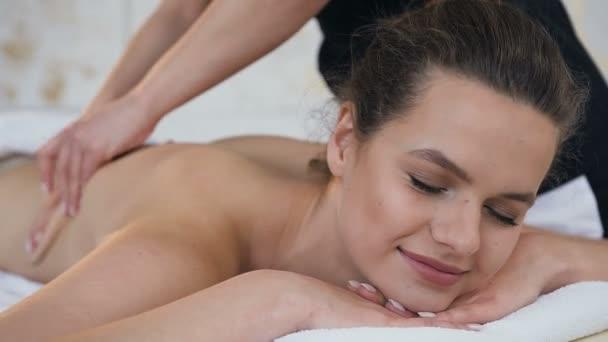 Vonzó kaukázusi nő relaxáló masszázs közben a hátsó Spa szalon.