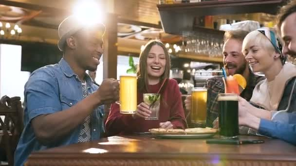 Five hipster friends clinking glasses with beer and cocktails in bar, pub.