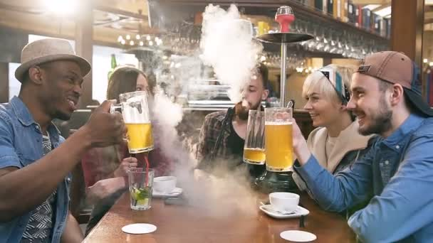 Company of hipster young people chatting, clinking with glass of beer and smoking shisha or hookah in bar.