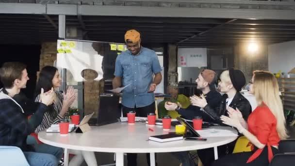 Rozmanitý tým tvůrčích vývojářů tleskal svému Afro-americkému kolegovi, který prezentoval na skleněné desce v zasedací místnosti. Pracovní debata, kreativní, práce a lidé