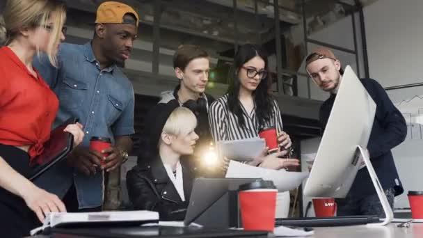 Mladý tým multietnických kreativních podniků provádí analýzu nových obchodních nápadů, diagramů a grafů, koncepce týmové práce v moderní kanceláři
