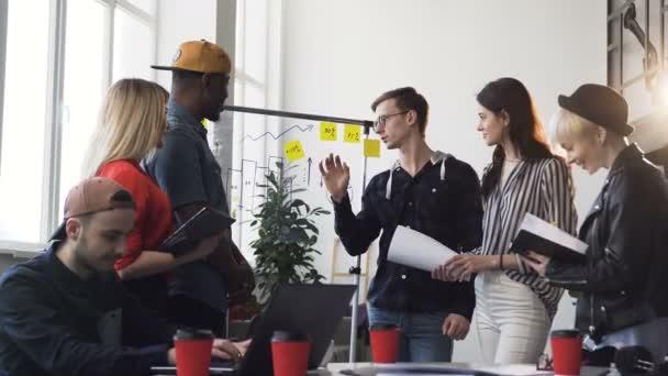 Tým multietnických obchodních lidí v příležitostných šatech analýza dat z diagramu na skleněné desce během pracovního dne v kanceláři