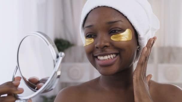 Közelről szép afro-amerikai nő, fehér törülközővel a fejét érvényes arany foltok szeme alatt, nézte a tükörbe. Szem bőrkezelés, Arcápolás