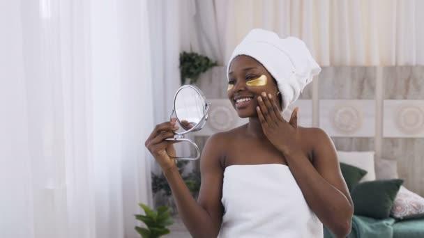 Krásná mladá africko-americká žena s bílým ručníkem v hlavě a přírodní make-upem se zlatými kolagenovými skvrnami na čerstvé obličejové kůži