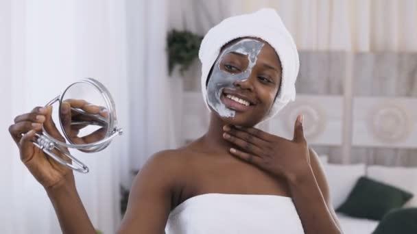 Portré fiatal mosolygós afrikai nő, fehér törülközővel a fej alkalmazott agyag maszkot fél arcon és figyeli a tükörben