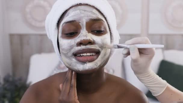 Nahaufnahme. Afroamerikanerin mit Handtuch auf dem Kopf, während Kosmetikerin Hand Maske auf ihr Gesicht mit speziellem Pinsel im Wellnesszentrum aufträgt