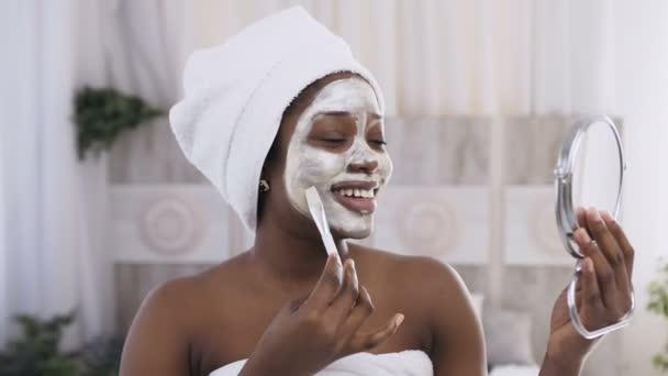 Portré csinos afro-amerikai nő törülközővel a fejét alkalmazó agyag maszkot a felét arc segítségével töltsük fel kefe és tükör. Arcápolás, fiatalítás, bőrápolás