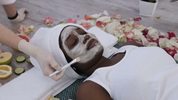 Fiatal afrikai nő egyre arc ellátás segítségével kozmetikus a szépségszalonban. Arc peeling maszk, Spa szépségápolási kezelés, bőrápoló