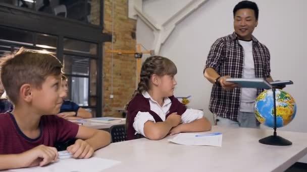 Mladý učitel základní školy při chůzi mezi stoly klade učebnice pro učení se na psacím stole, zatímco žáci sedí u stolů a připravují