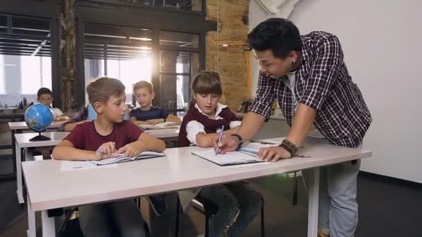 Mladý korejský učitel stojící poblíž školských dětí, kteří sedí u stolu ve třídě a v učebnici mu vysvětlují něco, co je v té lekci