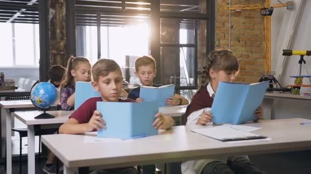 Skupina šesti kavkazských žáků, kteří sedí u oddělení a nezávisle studuje nové téma lekce z učebnice učebny ve třídě. Koncepce vzdělávání a lidí