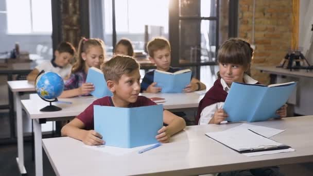 Lovely boy and girl of elementary school sitting at the desk looking each other smiling while reading book on lesson their classmates learning on back background