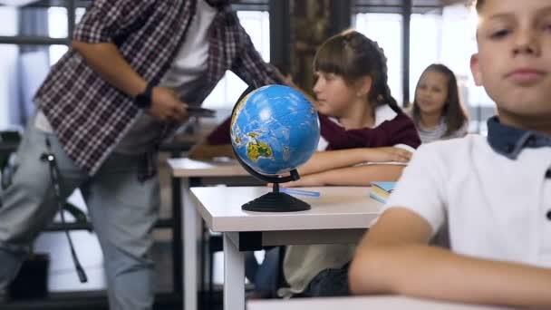 Mužská učitelka na základní škole při chůzi mezi stoly dává počítačům Tablet na stole pro výuku