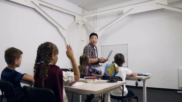 Kaukázusi iskoláslány figyelemfelkeltő és választ kérdésre a Koreai tanár során iskolai leckét ül az asztal mögött