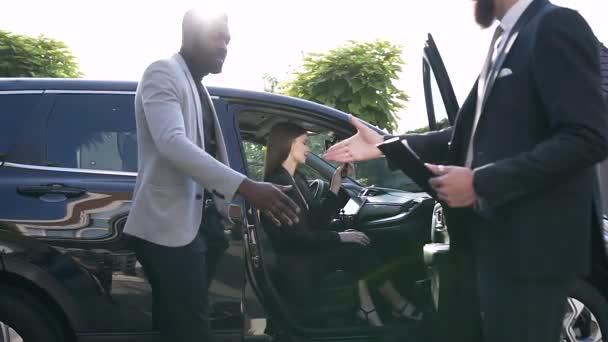 Šťastná žena, která drží klíč v autě uvnitř a muži potřásaje rukama a vstupují do akviziční smlouvy