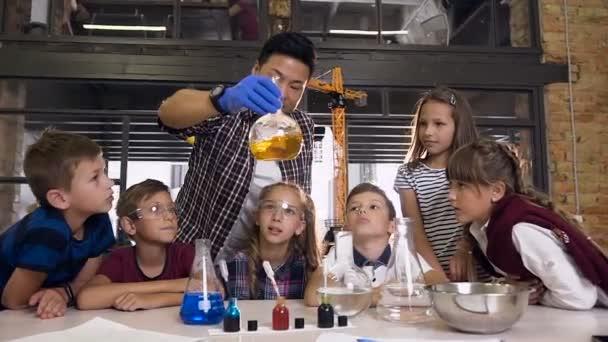 Scienziato che mostra ai ragazzi come fare esperimenti di reazione chimica in classe di laboratorio. Reazione chimica colore arancione in bicchieri fiaschetta. Scienza, chimica e scienziati
