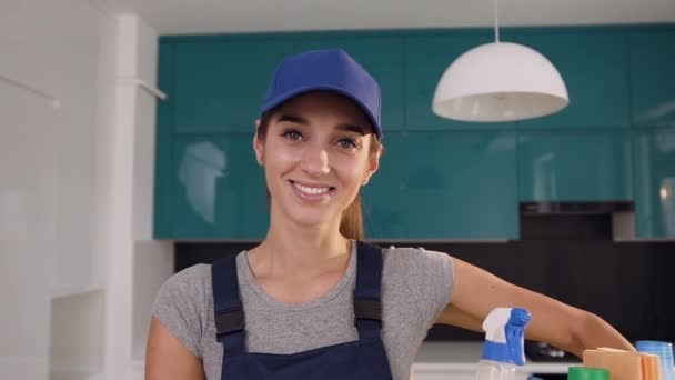 Lächelnde junge Frau in Spezialkleidung mit blauer Mütze, Korb mit Waschmitteln in der Hightech-Küche
