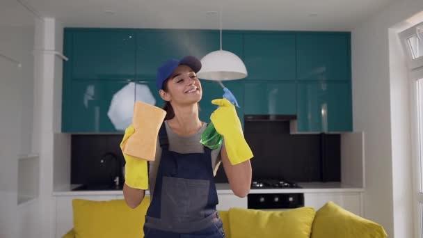 attraktive lächelnde Frau vom Putzdienst, die Spülmittel und Lappen in der Hand hält und Bewegung zum Fensterputzen zeigt