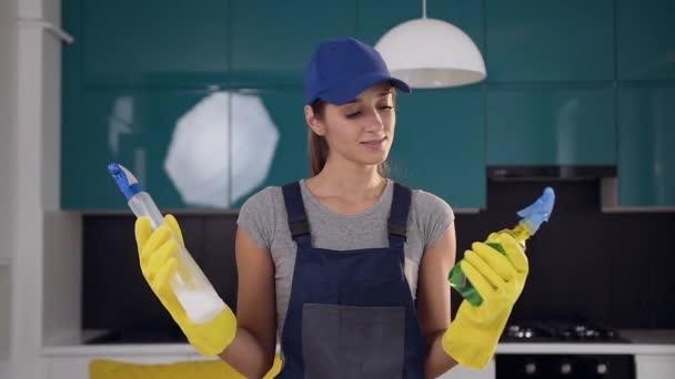 Mladá usměvavá žena z čištění, porovnávající dva čisticí prostředky v rukou uprostřed kuchyně