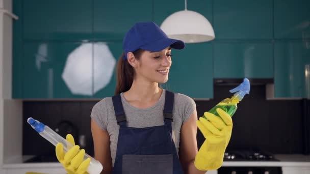 Atraktivní veselá žena v pracovním oblečení si vybírá zelený saponát mezi dvěma čisticími prostředky, který je v současné kuchyni