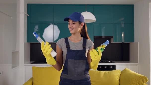 schöne junge Frau in Arbeitskleidung verwechselt zwischen zwei Flaschen Waschmittel, steht in der gemütlichen Küche