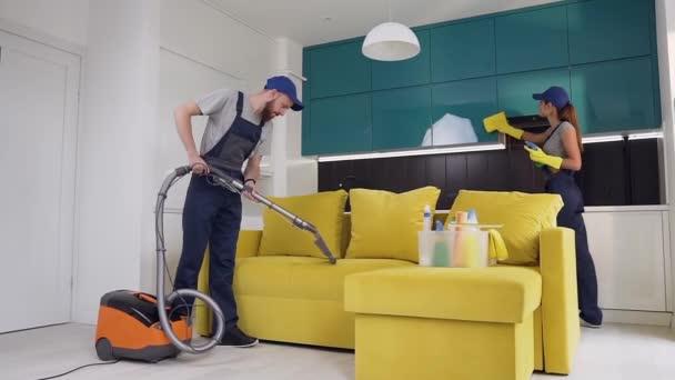 Atraktivní obrázek pracovníků z úklidové služby, kde člověk vysávat pohovku a ženu, která otírala nábytek