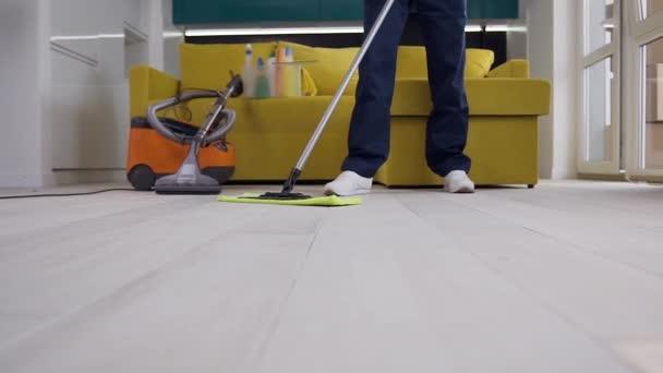 Obrázek nerozpoznatelného čisticího pracovníka v modrém stejnokroji mytí kuchyňské podlahy