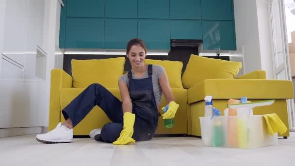 Usmívající se mladá žena ve speciálních šatech Stříkání detergentu na podlahu a stěrkou hadříkem
