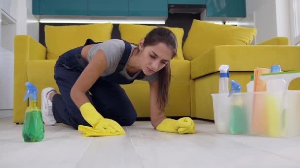 Zaměřovací pracovník na čištění žen v modrém rovnoměrném postřiku na podlahových pracích a s hadrem na kolenou