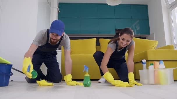attraktive Männer und Frauen der Reinigungsfirma, die die Reinigungsmittel auf den Holzboden sprühen und mit Lumpen wischen