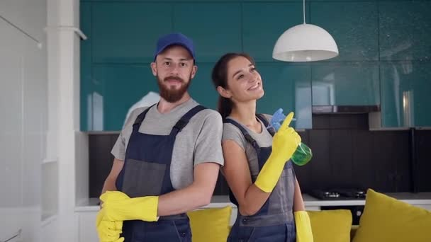 Lächelndes, gut aussehendes Team der Reinigungskräfte in blauen Uniformen, die in der Mitte der Küche stehen