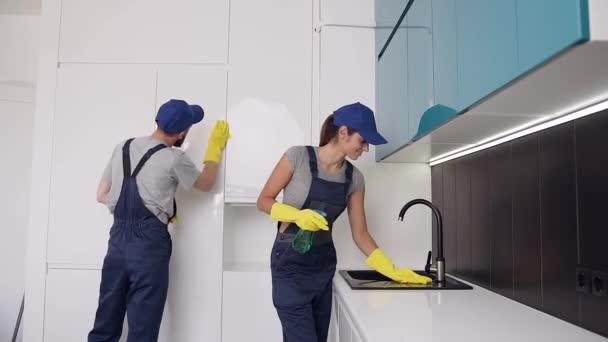 Hezký mladý pár z čisticího úřadu, který se stěním kuchyňského nábytku