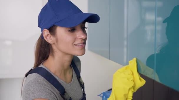 Krásná mladá ženská pracovnice čisticího zařízení oblečená v uniformě a žluté rukavice, které stějí kuchyňský nábytek