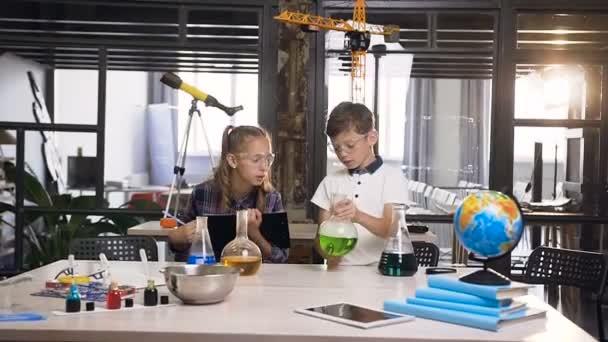Giovane ragazzo scientifico esamina due liquidi di colore diverso in un test flaconi mentre ragazza scientifica scrive formule chimiche durante gli esperimenti in classe