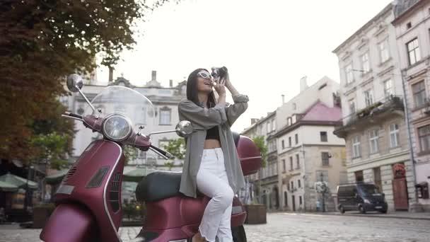 Charmant lächelnde Frau mit stylischer Sonnenbrille, die ein Foto vor der Kamera macht und auf dem modernen Roller sitzt