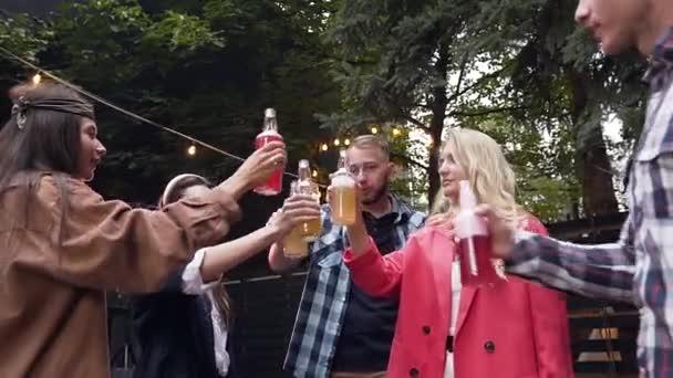 Atraktivní radostné mladé přátele, kteří odpočívají v zahradě a cinkuje lahve