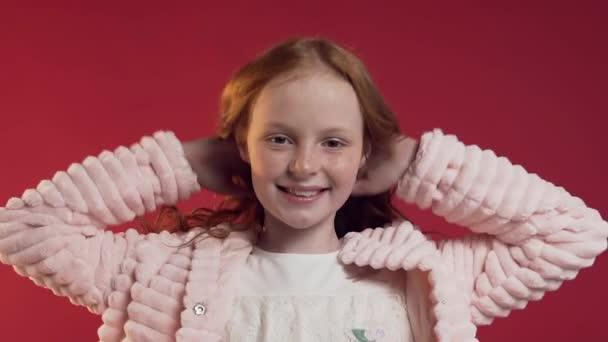 Nahaufnahme von entzückenden glücklichen Mädchen spielen mit ihren roten lockigen Haaren und Blick auf die Kamera an der roten Wand