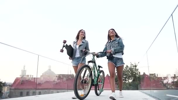 Pretty cheerful young ladies in fashion clothes walking with bicycle and skateboard on the glass observation deck
