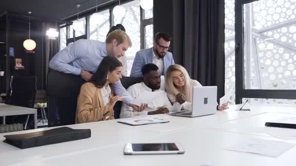 Účelně přijatelní multiraciální podnikatelé diskutující o společném počítačovém projektu v zasedací místnosti