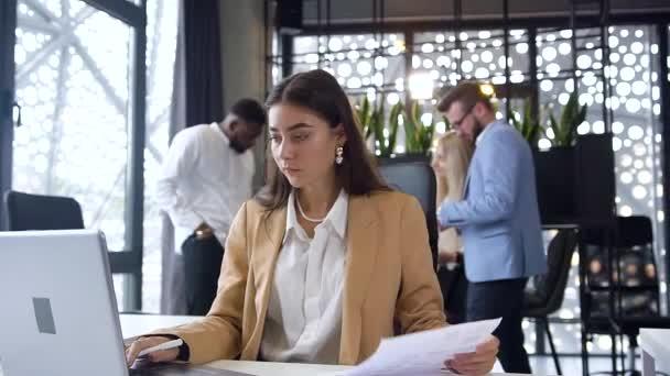 Detailní záběr půvabné mladé podnikatelky, která zadává data od sestavy k počítači v moderní kanceláři na pozadí kancelářských kolegů