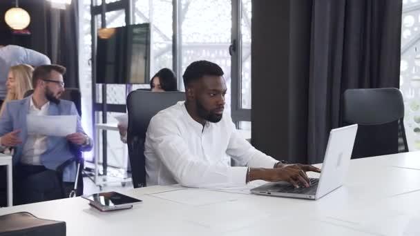 Účelný vousatý africký americký podnikatel pracující s papíry a počítačem u kancelářského stolu na pozadí svých obchodních kolegů